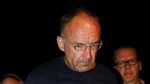 Douglas Garland is escorted into a Calgary police station in Calgary, Alta., Monday, July 14, 2014. (Jeff McIntosh / THE CANADIAN PRESS)