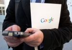 In this Dec.10 2013 file photo, a reporter uses his phone during a presentation for the new Google cultural institute in Paris, France. (AP/Jacques Brinon)
