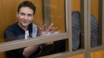 Ukrainian pilot Nadezhda Savchenko applauds and smiles in a glass cage inside court, in the town of Donetsk, Rostov-on-Don region, Russia, on March 22, 2016. (AP / Ivan Sekretarev)