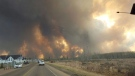 A wall of fire rages outside of Fort McMurray, Alta. Tuesday May 3, 2016 as a wildfire threatened the city. Raging forest fires whipped up by shifting winds sliced through the middle of the remote oilsands hub city of Fort McMurray Tuesday, sending tens of thousands fleeing in both directions and prompting the evacuation of the entire city. (Mary Anne Sexsmith-Segato / THE CANADIAN PRESS)