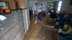 Shane Altzier starts to sweep out the mud from the town utilities office in Rainelle, W. Va. on Saturday, June 25, 2016. (AP / Steve Helber)