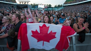 Fans sing the national anthem during Fire Aid for Fort McMurray in Edmonton, Alberta, on Wednesday June 29, 2016. (Amber Bracken / THE CANADIAN PRESS)