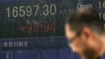 A man walks past an electronic stock board showing Japan's Nikkei 225 index at a securities firm in Tokyo, Japan on Wednesday, Aug. 24, 2016. (AP / Eugene Hoshiko)