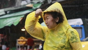 A woman struggles against powerful gusts of wind generated by typhoon Megi across the island in Taipei, Taiwan on Tuesday, Sept. 27, 2016. (AP / Chiang Ying-ying)