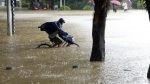 A man bicycles through a flooded street after the landfall of Typhoon Megi in Fuzhou in southeastern China's Fujian Province Wednesday, Sept. 28, 2016. (Chinatopix via AP)