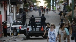 Municipal police trucks drive past strolling tourists, as they leave the Blue Parrot club, where several people were killed in early morning gunfire, in Playa del Carmen, Mexico on Monday, Jan. 16, 2017. (AP / Rebecca Blackwell)